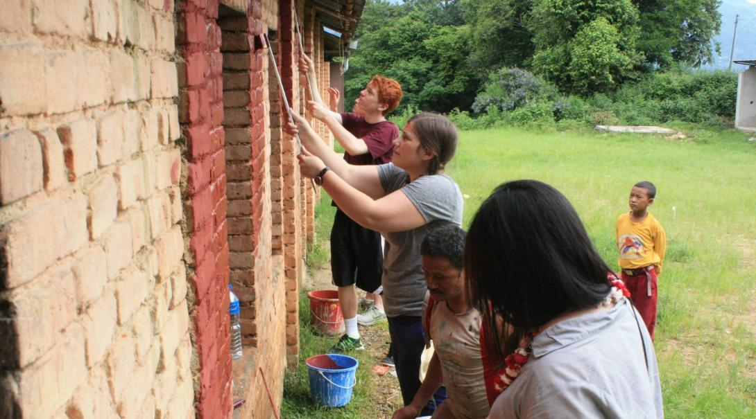 Building volunteers paint the wall of a new classroom in Nepal